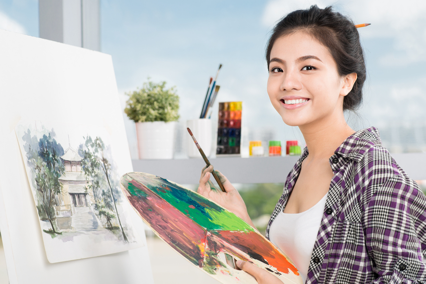 Young Asian woman working on painting in a workshop