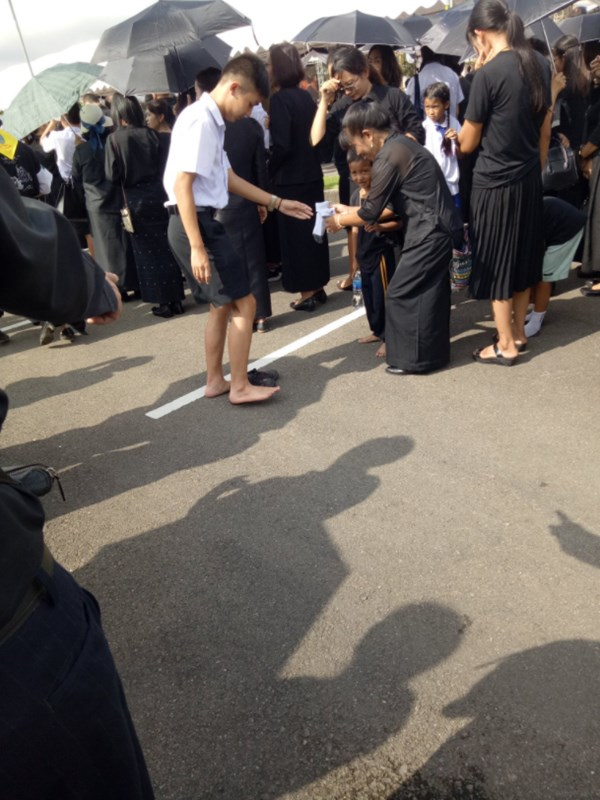 นักเรียนชาย สละถุงเท้าให้เด็ก ที่ยืนเท้าเปล่ากลางแดด งานพระราชพิธีฯ